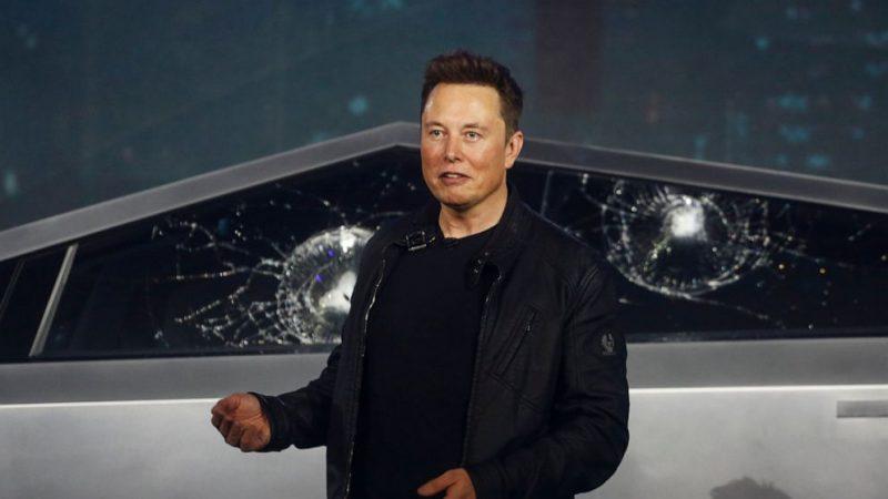 """Bu fotoğrafta Elon Musk, 21 Kasım 2019 tarihinde Kaliforniya Hawthorne'daki Tesla tasarım stüdyosunda yeni aracı olan Cybertruck'ı tanıtıyor. Musk bu en yeni ve en farklı tasarıma sahip olan elektrikli aracıyla birlikte ağır vasıta kamyonet pazarına girmektedir. Tesla'nın bu oldukça ses getiren araç tanıtımına metal topla cam kırılmazlık testinin başarısızlığı perşembe gecesine büyük bir damga vurmuştur. Otomobil lansmanlarının en utanç verici anları listesinde en üst sırada yerini alan bu olay, Musk'ın """"Cybertruck"""" üstündeki """"Tesla Armor Glass ( Zırh kaplı Cam)"""" tanıtımında ürününün gücünü methederken yaşanmıştır."""
